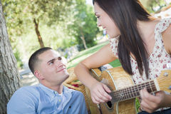 Mixed Race Couple at the Park Playing Guitar and Singing Royalty Free Stock Photography