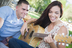 Mixed Race Couple at the Park Playing Guitar and Singing Stock Photo