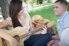 Mixed Race Couple at the Park Playing Guitar and Singing Stock Images