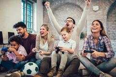 Mixed race couple play video games with their children royalty free stock photography