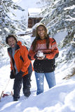 Mixed race couple playing in snow with snowball and sled stock image