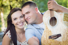 Mixed Race Couple Portrait with Guitar in Park Royalty Free Stock Photography