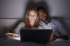 Mixed race couple relax in bed with laptop, drinks and snacks Royalty Free Stock Images
