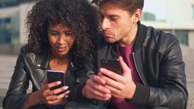 Couple sharing mobile phones stock video footage