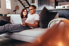 Couple relaxing on sofa at home with laptop. Mixed race couple sitting on a couch with laptop in living room. Couple relaxing on sofa at home using laptop Stock Images