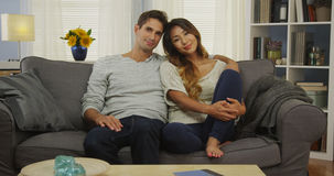 Mixed race couple sitting on couch smiling Stock Image