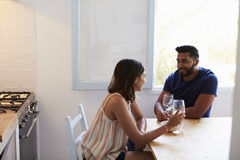 Mixed race couple sitting in kitchen and drinking wine Stock Images