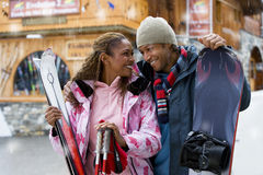 Mixed race couple with snow skis Royalty Free Stock Photos
