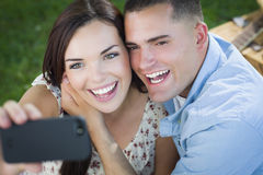 Mixed Race Couple Taking Self Portrait in Park Stock Photos