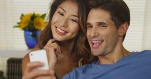 Mixed Race couple taking selfies Stock Photo