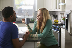Mixed race couple talking over breakfast in the kitchen Royalty Free Stock Photography