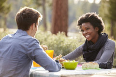 Mixed race couple talking at a picnic table, close up Stock Photos
