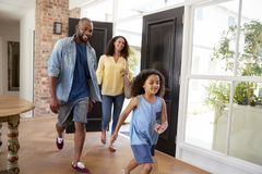 Mixed race couple and their daughter arriving home stock photo