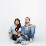 Mixed race couple thinking looking up and sitting on the floor. A portrait of a mixed couple thinking looking up and sitting on the floor Stock Photography