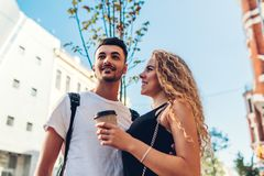 Mixed race couple of tourists walking in city. Arab man and white woman drinking coffee and hugging outdoors. royalty free stock image