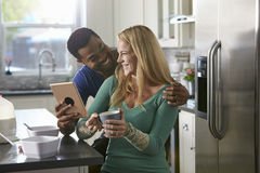 Mixed race couple using a tablet computer look at each other Stock Image