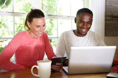 Mixed race couple using wireless technology at home Royalty Free Stock Images