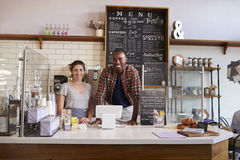 Mixed race couple waiting behind counter at a coffee shop stock image