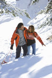 Mixed race couple walking in snow with sled Royalty Free Stock Images