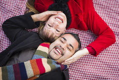 Mixed Race Couple Wearing Winter Clothing on Picnic Blanket in a Park Stock Image