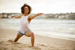 Mixed-race dancer stretching on the beach. Young mixed-race dancer smiling while stretching on the beach Royalty Free Stock Photo