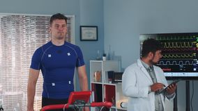 Mixed race doctor performing stress test while the athlete walking on treadmill. Computer supervises whole test process stock video footage