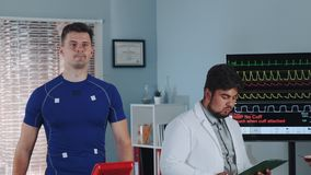 Mixed race doctor reading something while athlete treadmill testing on racetrack. Lab displays showing EKG data stock video footage