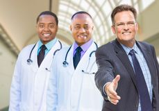 Mixed Race Doctors Behind Businessman Reaching for Hand Shake In Royalty Free Stock Photography