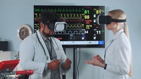 Mixed race doctors in VR glasses discussing about something in modern sports lab. With EKG data on display in the background stock footage