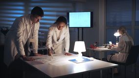 Mixed race electronics engineers in white coats discussing control electronics scheme in laboratory. There is a big TV screen in the background stock footage