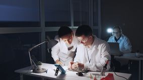 Mixed race electronics engineers in white coats working on motherboard using multimeter tester. Man is in protective glasses stock video footage