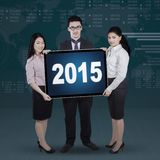 Mixed race entrepreneurs holding numbers 2015 Stock Photos