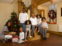 Mixed race family with Christmas tree and gifts. Smiling at camera stock photography