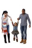 Mixed race family with cute little girl walking. Mixed race family walking, father and mother swinging little daughter between them royalty free stock image