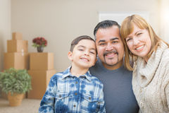 Mixed Race Family In Empty Room With Moving Boxes and Plants. Mixed Race Family In an Empty Room With Moving Boxes and Plants Royalty Free Stock Photo