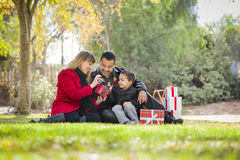 Mixed Race Family Enjoying Christmas Gifts in the Park Together Royalty Free Stock Image