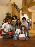Mixed race family exchanging gifts at christmas. Smiling at camera stock images
