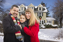 Mixed Race Family in Front of House in The Snow. Happy Young Mixed Race Family in Front of Beautiful Snow Covered House royalty free stock photography