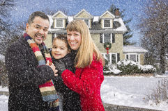 Mixed Race Family in Front of House in The Snow Royalty Free Stock Photo