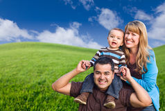 Mixed Race Family In Green Grass Field Stock Images