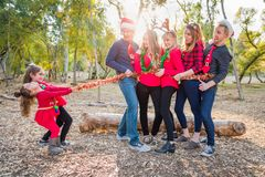 Mixed Race Family Portrait With Children Tying Up Group. Fun Mixed Race Family Portrait With Children Tying Up Group With Tinsel Rope stock photography