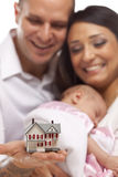 Mixed Race Family with Small Model House. Young Attractive Happy Mixed Race Family with Baby and Small Model House royalty free stock photography