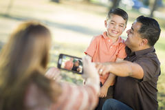 Mixed Race Family Taking Pictures with a Smart Phone Camera. Happy Mixed Race Family Taking A Phone Camera Picture At The Park stock photo