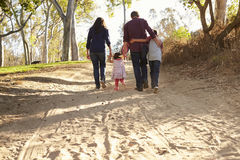 Mixed race family walking on rural path, back view Royalty Free Stock Photography