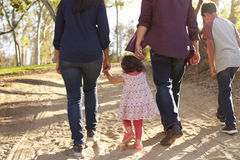 Mixed race family walking on a rural path, back view, crop Royalty Free Stock Photos