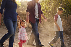 Mixed race family walking on rural path, close up side view royalty free stock photo