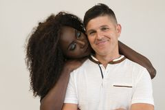 Mixed race family. Young tender wife hugging his husband. Loving stock image