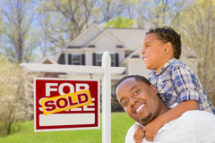 Mixed Race Father and Son In Front of Real Estate Sign and House Royalty Free Stock Photos