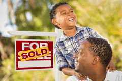 Mixed Race Father and Son In Front of Sold Real Estate Sign royalty free stock image