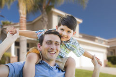 Mixed Race Father and Son Piggyback in Front of House. Mixed Race Father and Son Playing Piggyback in Front of Their House Royalty Free Stock Photo